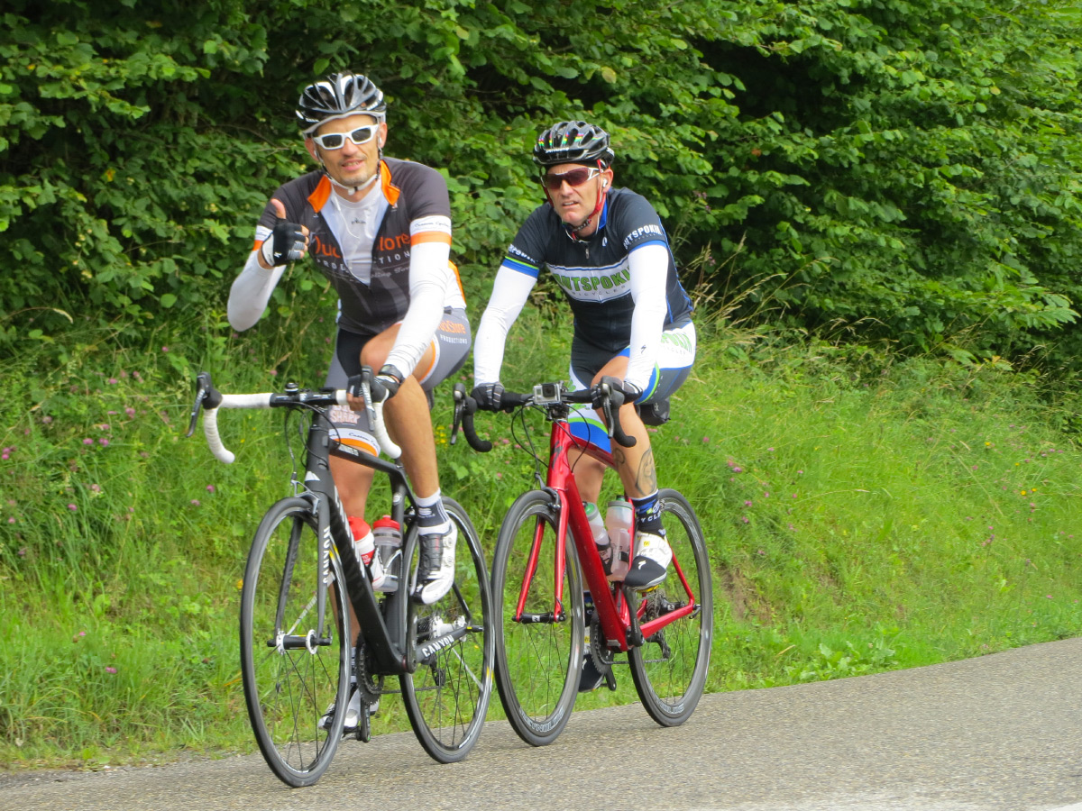 Two cyclists riding up Col de Leschaux above Lake Annecy